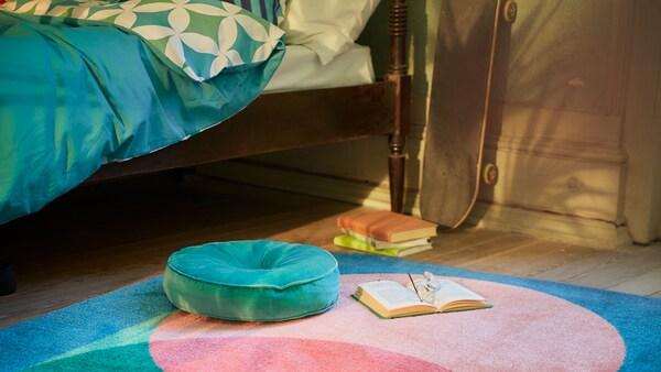 Une chambre avec des textiles GRACIÖS dans des tons turquoise, dont une housse de couette, un tapis à motifs et un coussin en velours rond.