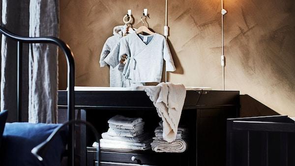 Une chambre avec des vêtements pour bébé accrochés au mur, au-dessus d'une table à langer.