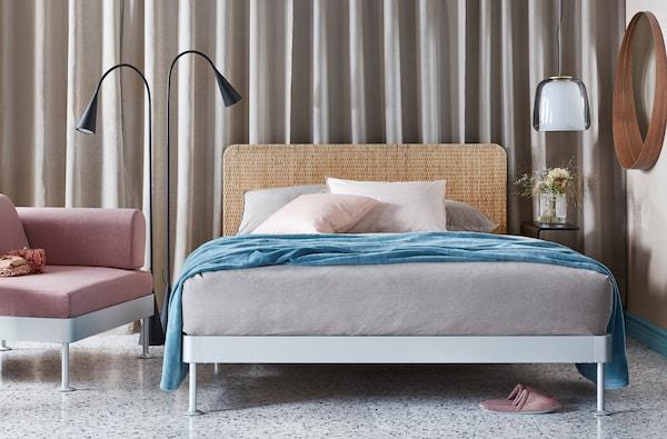 une chambre avec un lit des oreillers et du linge de lit a cote d