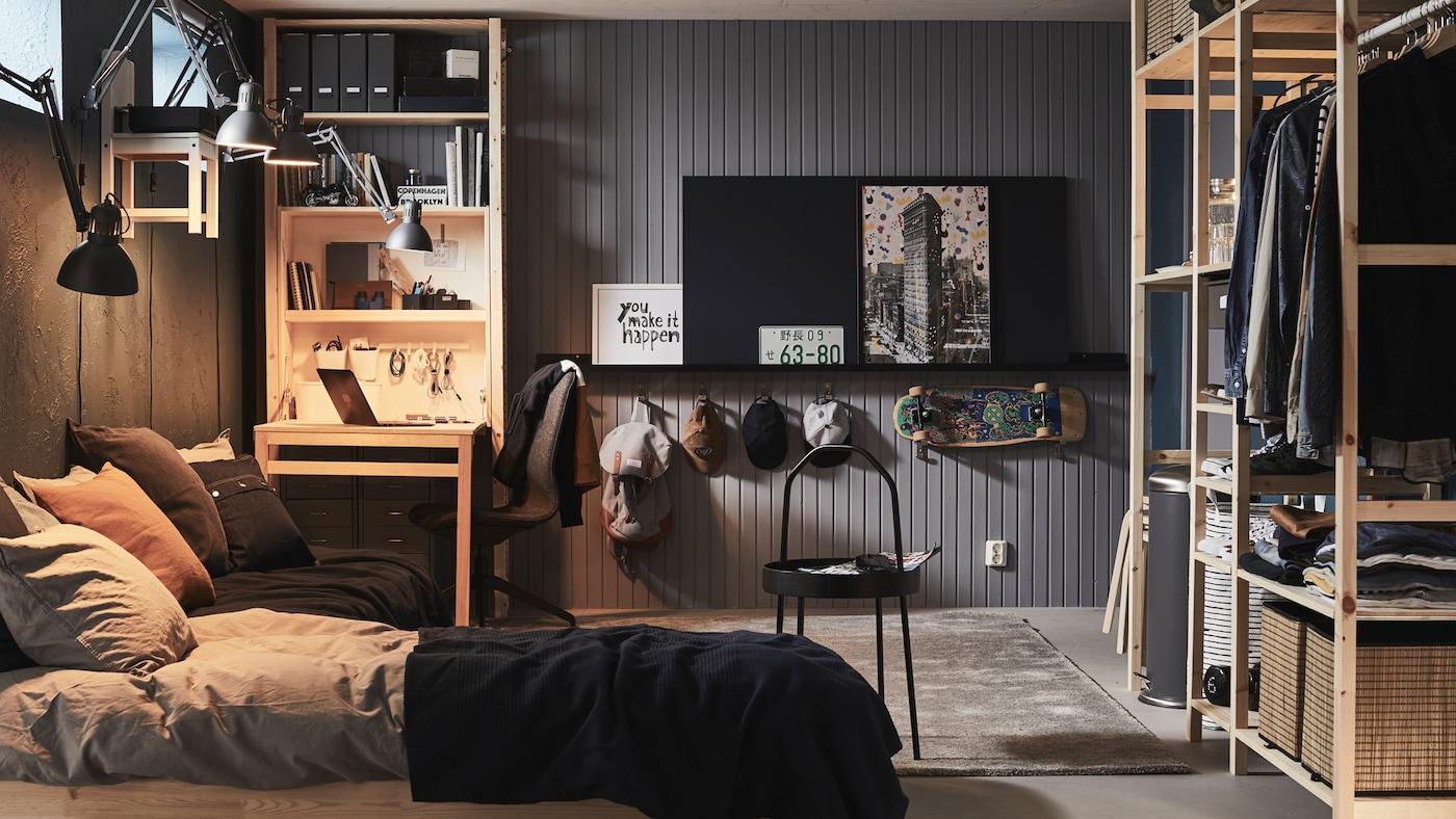 Une chambre avec un lit et des rangements, notamment une combinaison d'étagèresIVAR et un élément de rangement IVAR doté d'une table pliante.