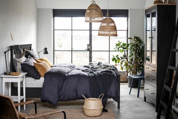 Une chambre avec un lit foncé HEMNES au centre, une porte-fenêtre et des détails de matières naturelles et de couleurs.