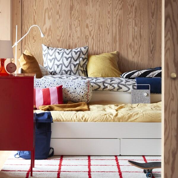 Une chambre d'adolescent dotée d'une structure de lit SLÄKT blanche, de coussins et de housses de couette de différentes couleurs, avec un tapis rouge et blanc et un sac bleu.