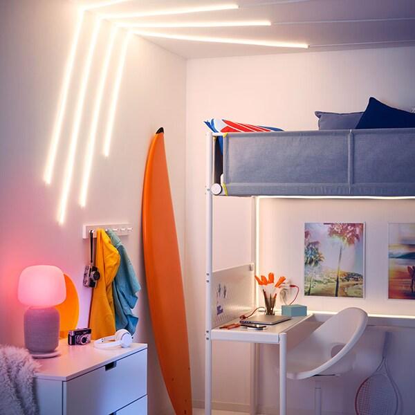 Une chambre d'enfant avec des bandes lumineuses au plafond et une lampe de table haut-parleur SYMFONISK.