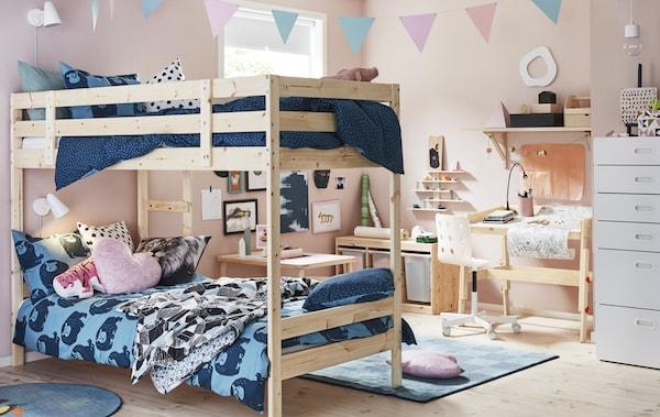 Une chambre d'enfant avec des murs roses, des lits superposés avec du linge de lit bleu, un bureau et des rangements en bois clair.