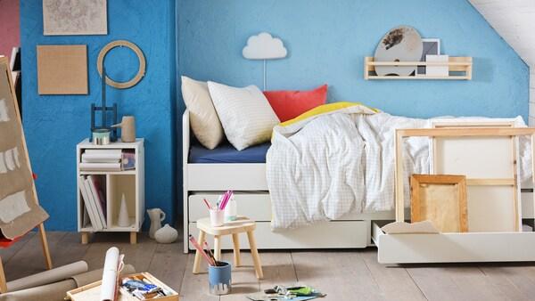 Une chambre d'enfant avec des outils d'artiste, une taie d'oreiller et une housse de couette VÄNKRETS. Il y a aussi une table de chevet avec étagères SMUSSLA blanche.
