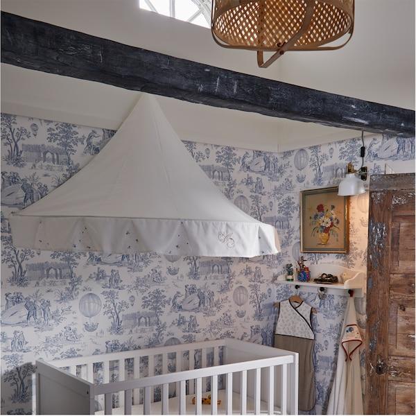 Une chambre d'enfant avec un ciel de lit blanc au-dessus d'un lit bébé, une suspension en bambou et du papier peint blanc avec un motif bleu.