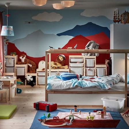 Une chambre d'enfant avec un lit en pin, un mur sur lequel des montagnes sont peintes, un tapis avec un bateau comme motif et beaucoup de peluches.