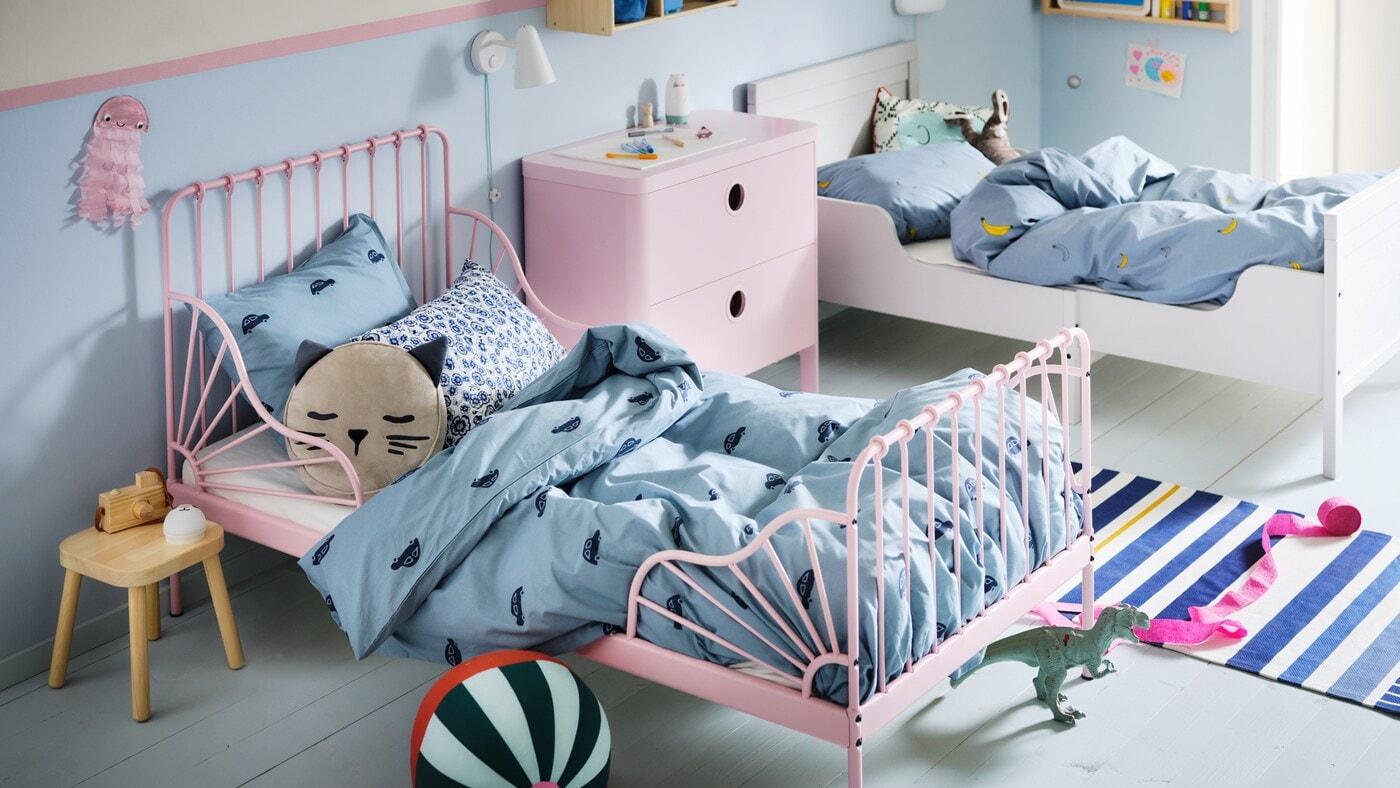 Une chambre d'enfant avec un lit évolutif MINNEN rose pâle et un lit blanc à la literie VÄNKRETS et BARNDRÖM bleue.