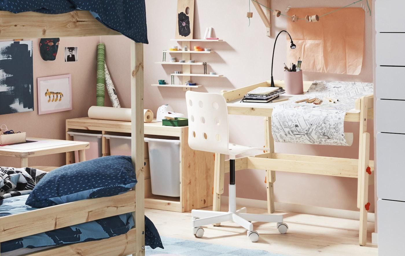 Une chambre d'enfant décorée/peinte en rose pâle avec des meubles en bois clair comprenant un bureau et des lits superposés.