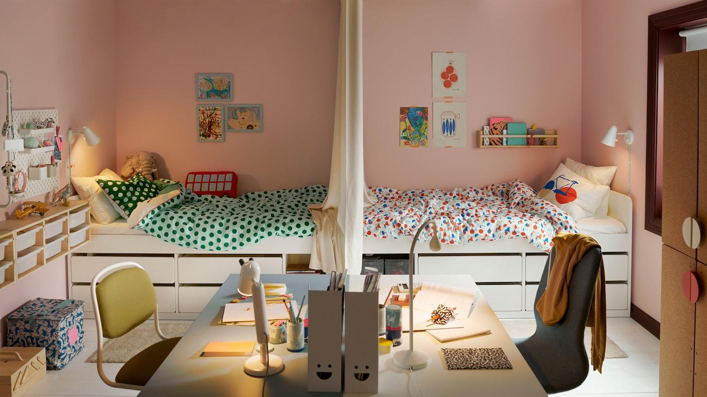 Une chambre d'enfant partagée divisée en deux, des lits installés face à face à l'arrière-plan et deux bureaux installés face à face à l'avant-plan.