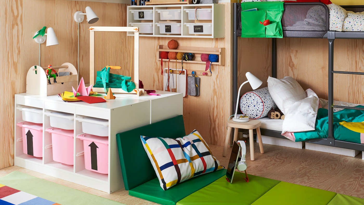 Une chambre d'enfants avec des lits superposés TUFFING, des rangements TROFAST et une zone d'assise confortable constituée d'un tapis de gymnastique pliant PLUFSIG.