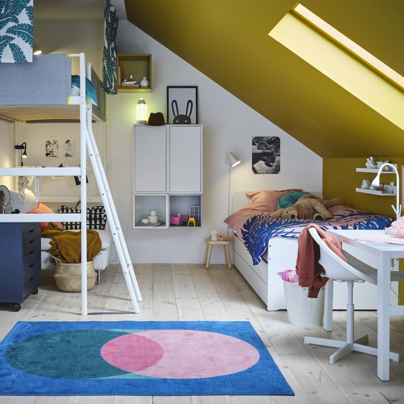 Une chambre d'enfants avec un lit mezzanine, un cadre de lit blanc, des armoires murales et rangements ouverts, un bureau blanc et un tapis rose/vert sur fond bleu.