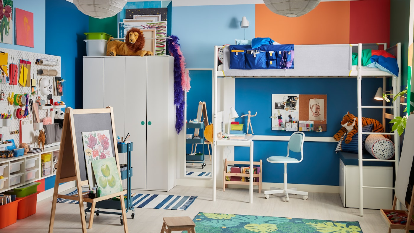 Une chambre d'enfants avec un lit mezzanine VITVAL blanc à bureau intégré dessous, un chevalet MÅLA et différents rangements.