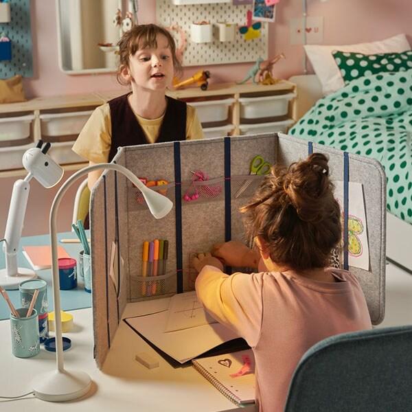 Une chambre d'enfants partagée avec deux bureaux l'un contre l'autre.