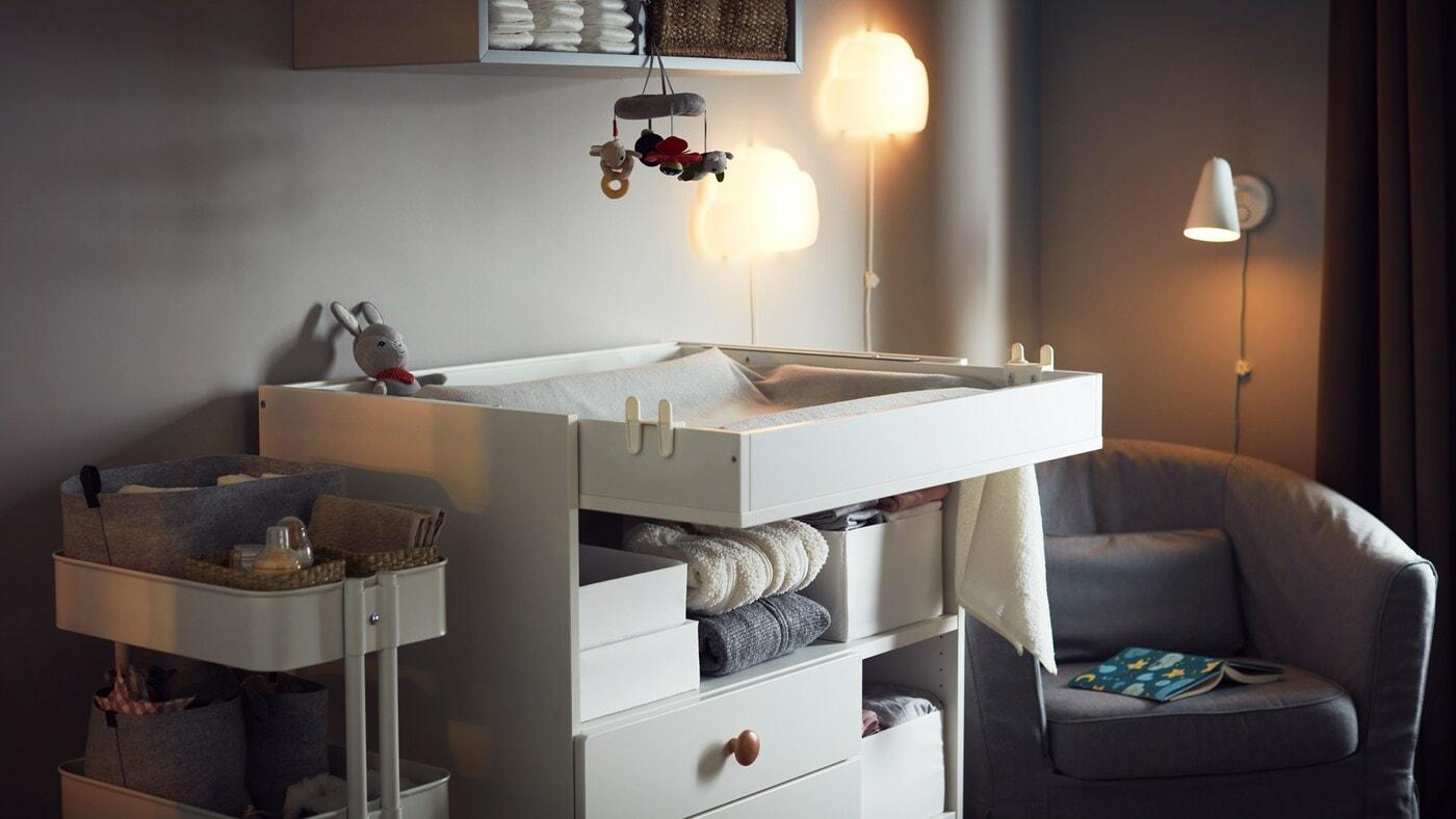 Une chambre douillette avec une table à langer, une desserte avec des accessoires pour bébé, un fauteuil, des appliques et du rangement mural.