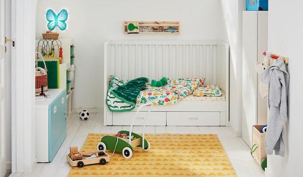 Une chambre enfant aménagée avec des meubles blancs, un tapis jaune et des jouets