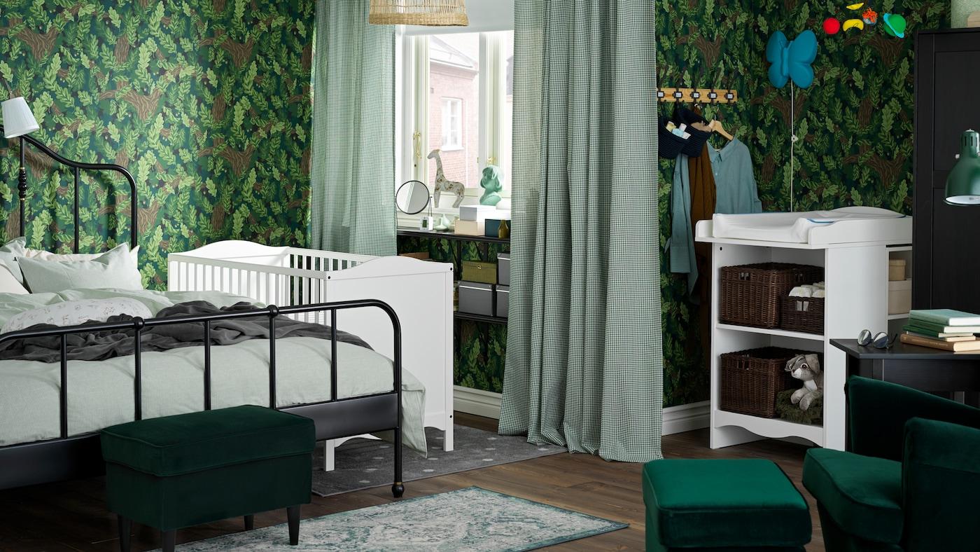 Une chambre familiale où un lit deux places SAGSTUA est posé près d'un lit enfant SMÅGÖRA blanc et d'une table à langer SMÅGÖRA.