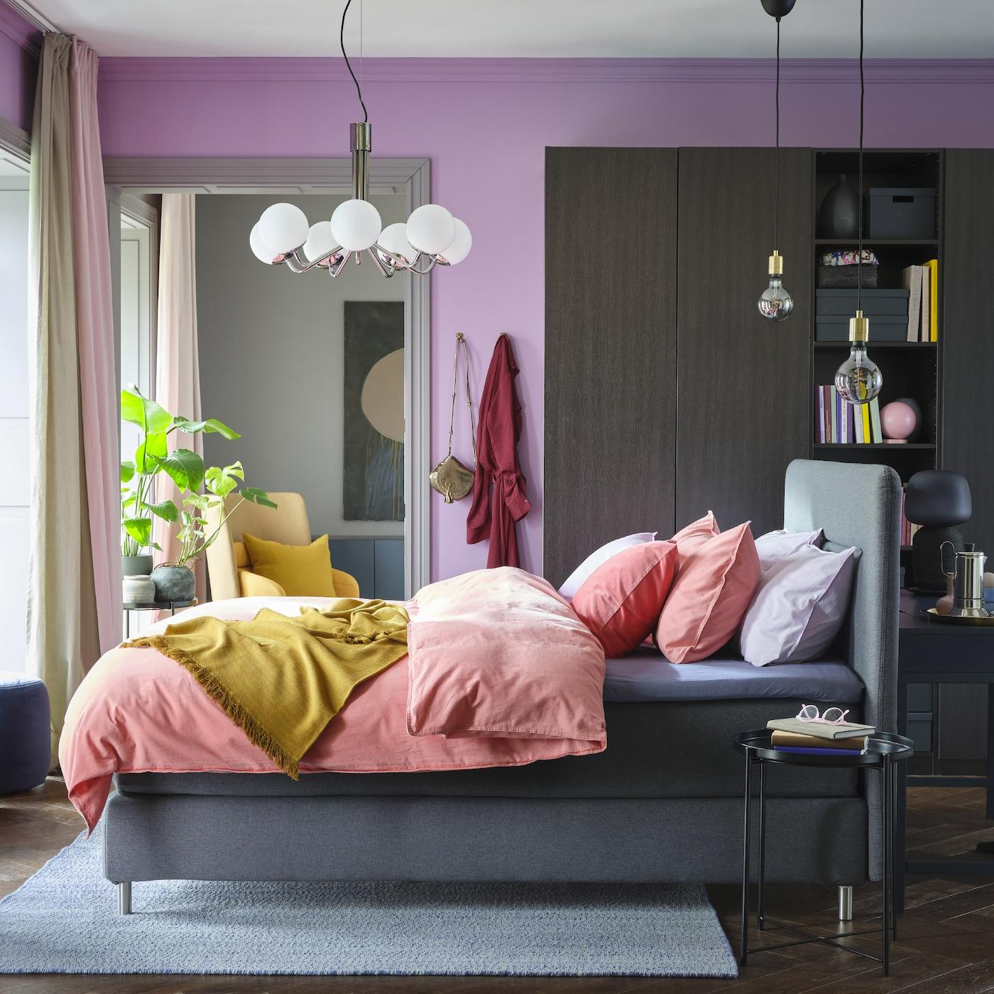Une chambre haute en couleurs: murs mauves, linge de lit rose clair et mauve, plaid couleur moutarde, armoire brun-noir et lit-sommier gris.