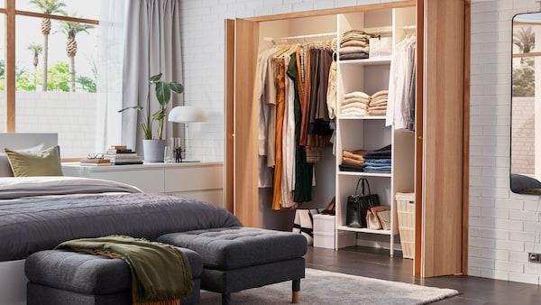 Une chambre lumineuse avec une armoire-penderie ajustée AURDAL, un lit blanc MALM avec literie grise et deux repose-pieds gris foncé MORABO.