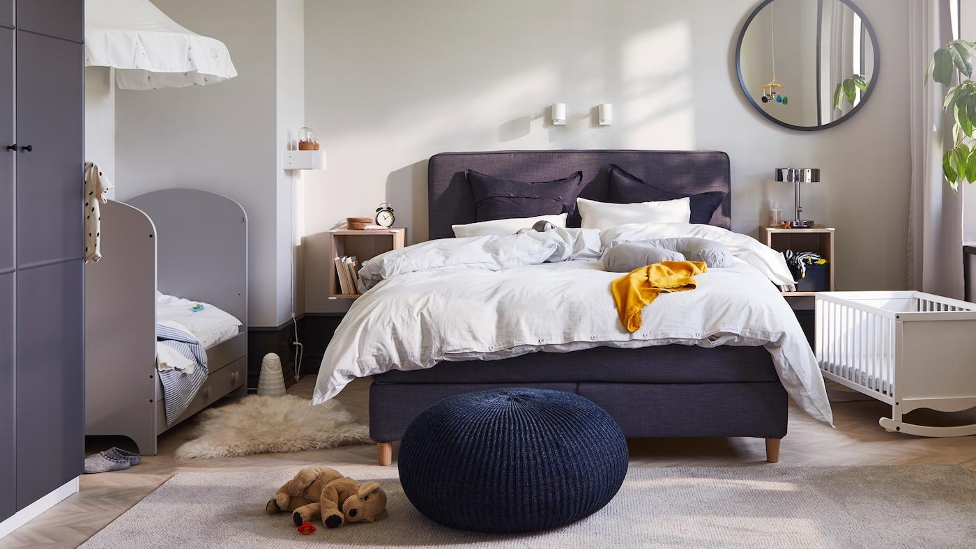 Une chambre partagée pour des parents avec deux enfants où un lit sommier tapissier DUNVIK est posé entre un lit enfant GONATT et un berceau SOLGUL blanc.