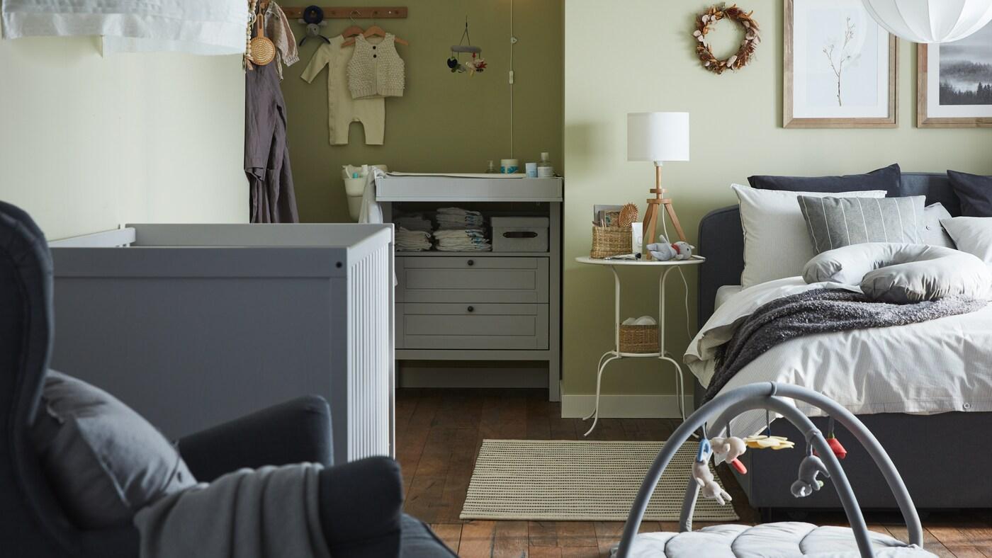 Une chambre pour parents et bébé avec un lit matelassé gris, un lit à barreaux gris, une commode/table à langer grise et des murs verts.