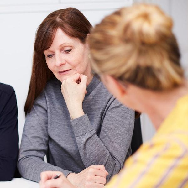 Une collaboratrice IKEA vêtue d'un haut jaune en pleine discussion avec une cliente, prenant des notes avec un stylo.