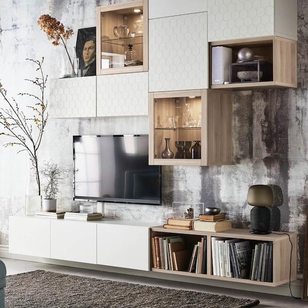 Une combinaison de rangement dans le salon avec différents modules du système BESTA en chêne blanc et blanc émaillé avec vitrine, armoires ouvertes et fermées