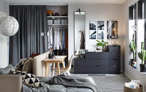 Une commode anthracite NORDLI à 9 tiroirs, contre un mur, au fond d'un petit espace de vie meublé d'un convertible et d'un bureau.