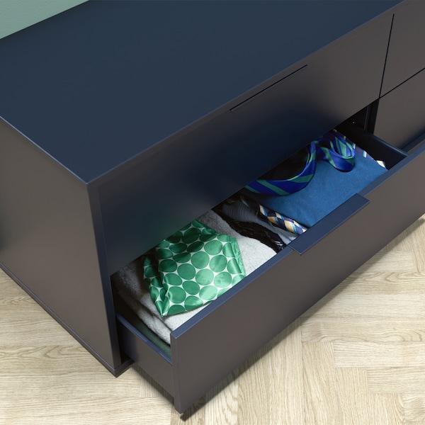 Une commode basse avec un tiroir ouvert qui révèle des vêtements pliés.