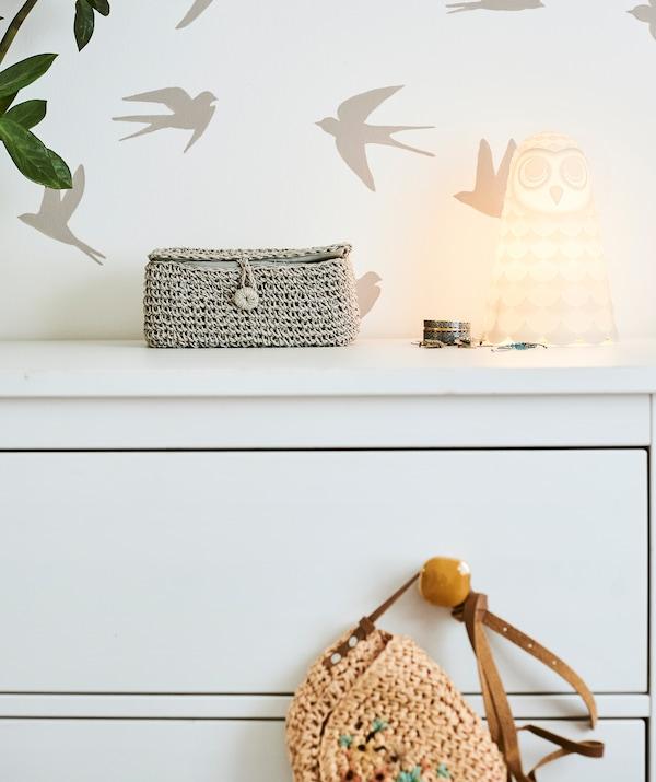 Une commode blanche avec poignées de couleur ambre et une lampe en forme de chouette sur le dessus, poussée contre un mur avec motif d'oiseaux au pochoir.