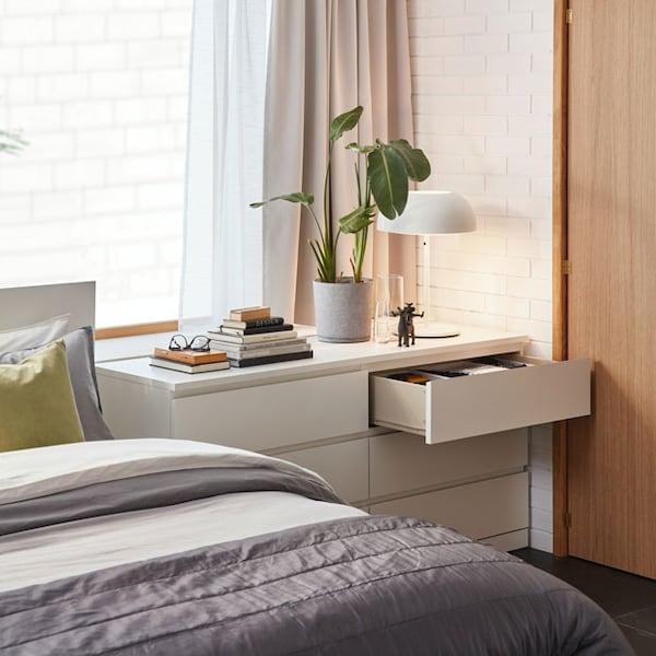 Une commode blanche MALM avec un lit confortable à côté et une plante, quelques livres et une lampe de table blanche NYMÅNE sur le dessus.