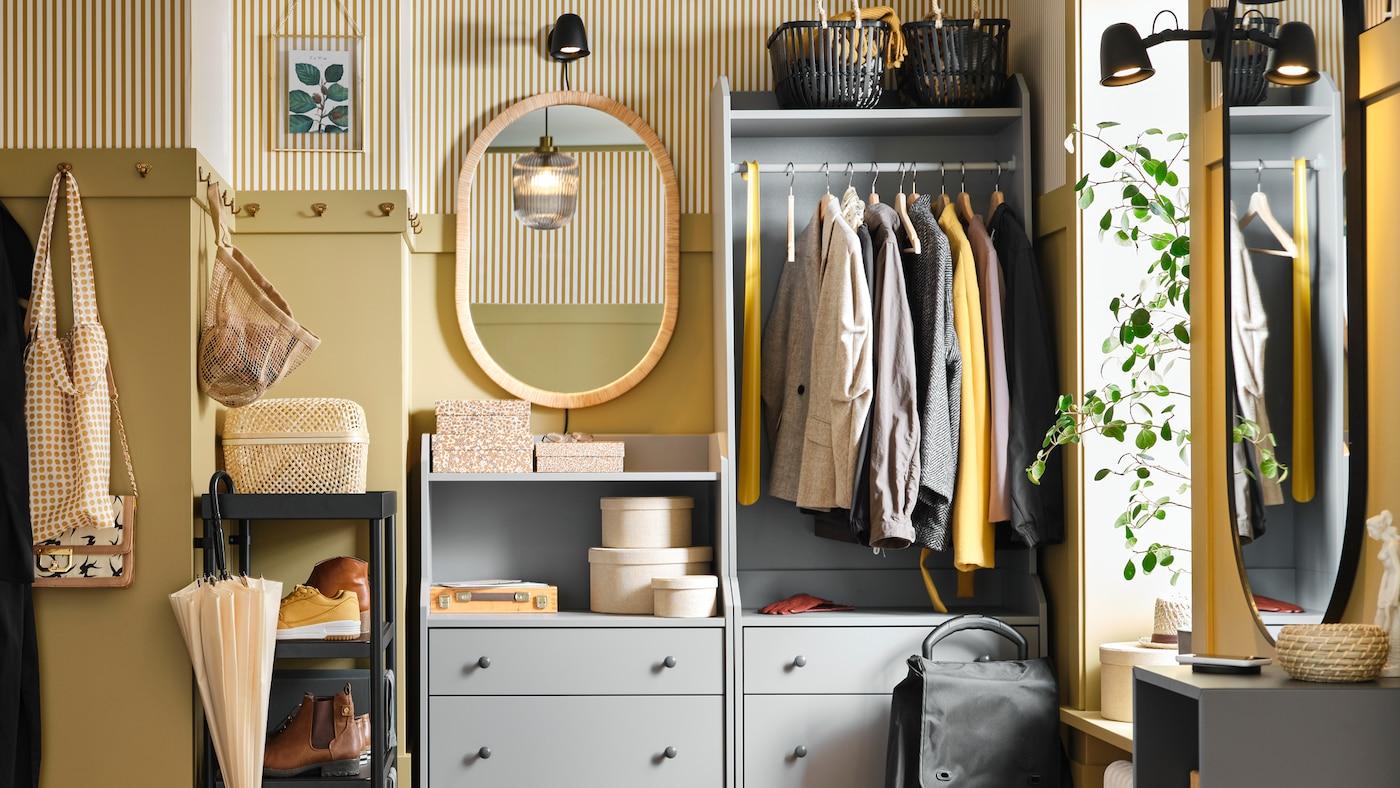 Une commode et une armoire-penderie ouverte HAUGA contenant des vêtements, des boîtes et des paniers dans un petit couloir.