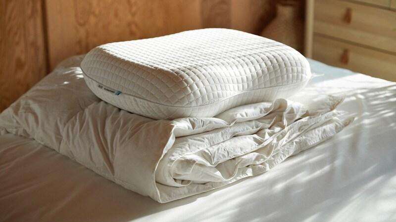 Une couette blanche et un oreiller ergonomique sur un lit.