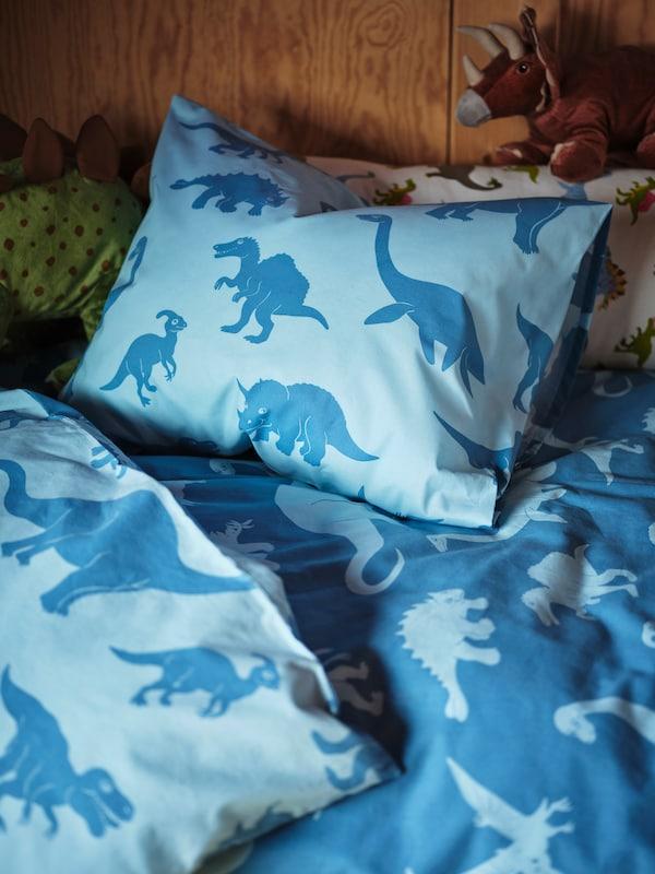 Une couette et un oreiller bleu clair et bleu foncé sont placés sur le lit d'un enfant, et deux dinosaures JÄTTELIK surgissent.