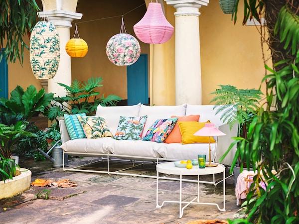 Une cour classique dans un ancien palais avec de nombreuses plantes et un canapé confortable avec des coussins et des lanternes colorés.