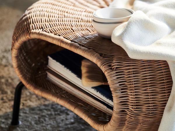 Une couverture blanche et trois bols blancs sur un repose-pieds GAMLEHULT à l'intérieur duquel sont rangés des livres.