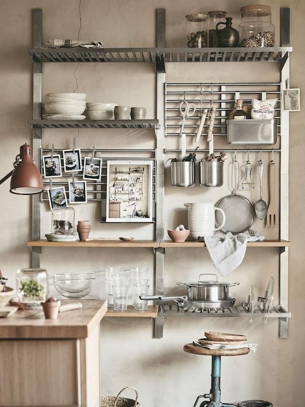 Une cuisine à aire ouverte où se trouvent des rangements muraux en acier inoxydable.