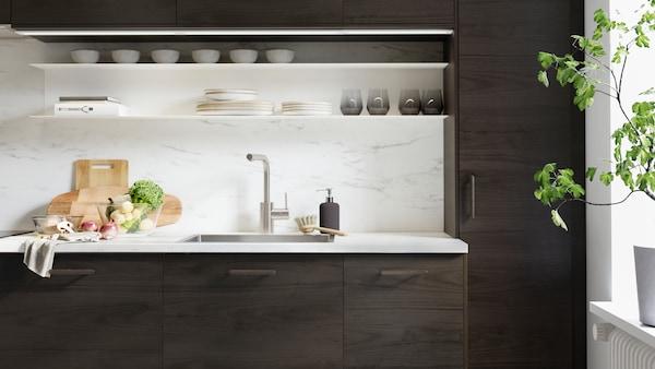 Une cuisine ASKERSUND à effet frêne marron foncé avec des planches à découper et des légumes sur un plan de travail EKBACKEN à effet marbre.
