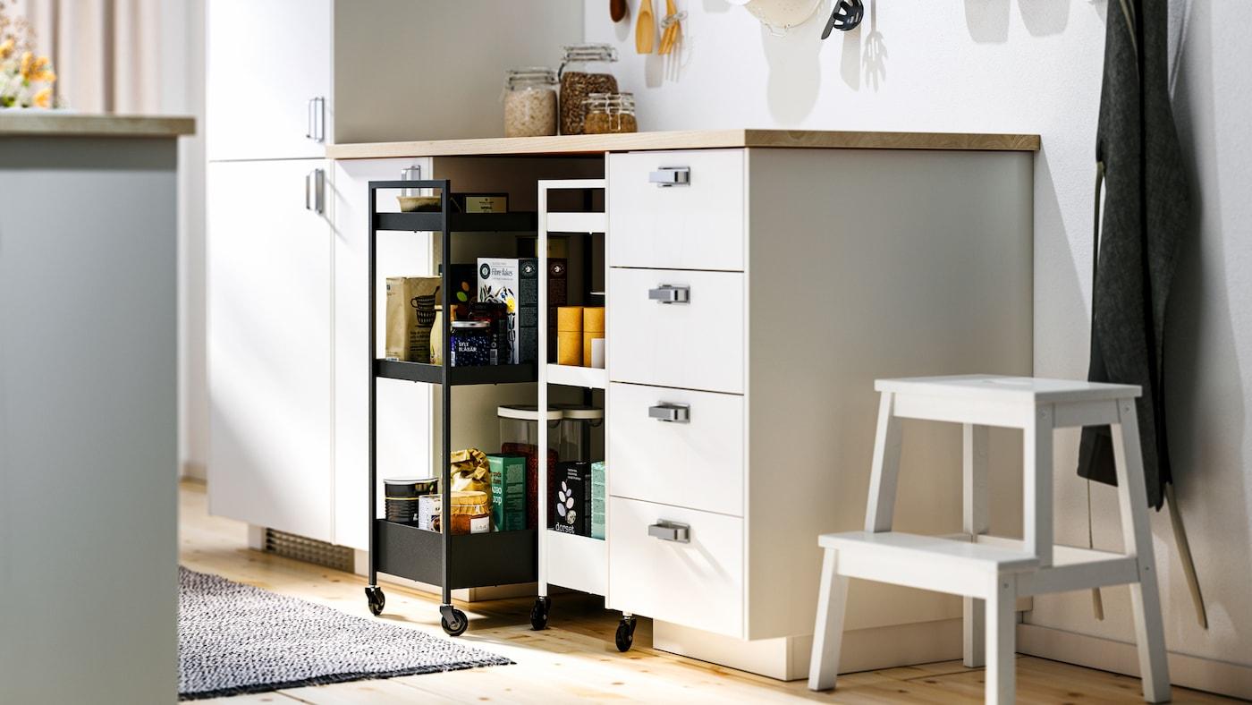 Une cuisine avec des armoires basses METOD blanches et des aménagements intérieurs MAXIMERA, un plan de travail EKBACKEN et deux dessertes NISSAFORS.