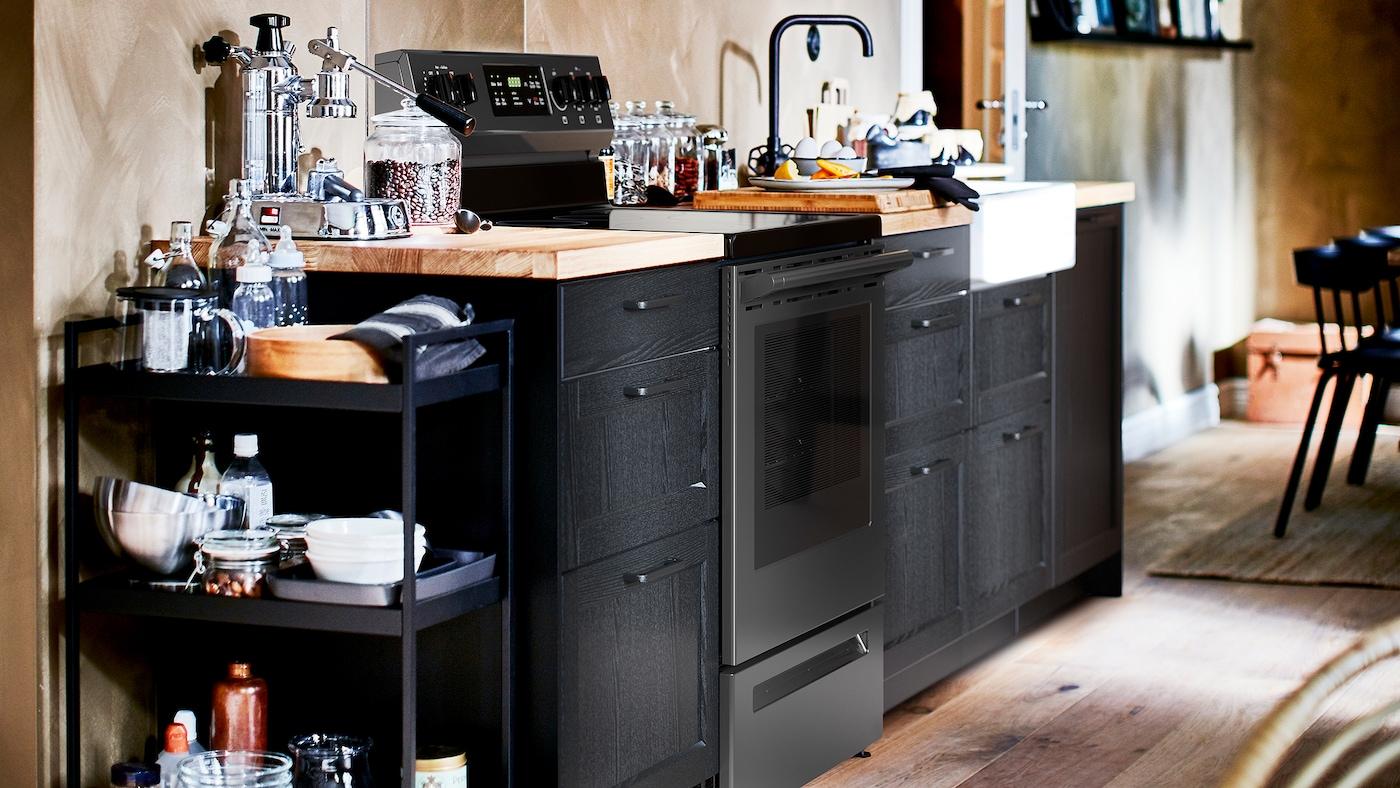 Une cuisine avec des façades d'armoires LERHYTTAN teintes en noir, un comptoir en chêne plaqué et un évier blanc dont l'avant est visible.