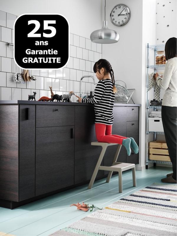 Une cuisine avec des murs carrelés blancs et des tiroirs ASKERSUND marron foncé. Une jeune fille joue avec des jouets sur le plan de travail.