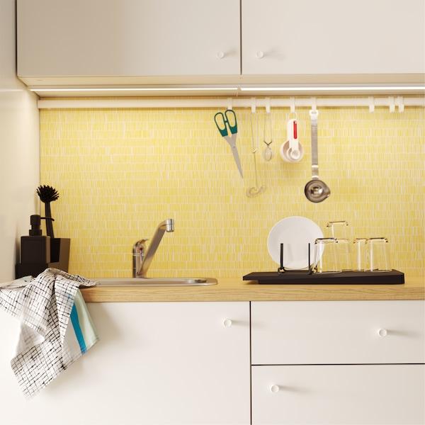 Une cuisine avec des portes blanches, une crédence jaune et une barre avec des crochets pour suspendre des ciseaux et autres ustensiles.