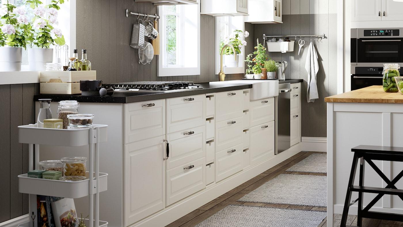 Une cuisine avec des portes et des façades de tiroirs blanc cassé, un comptoir à effet minéral noir et une table de cuisson au gaz en acier inoxydable.