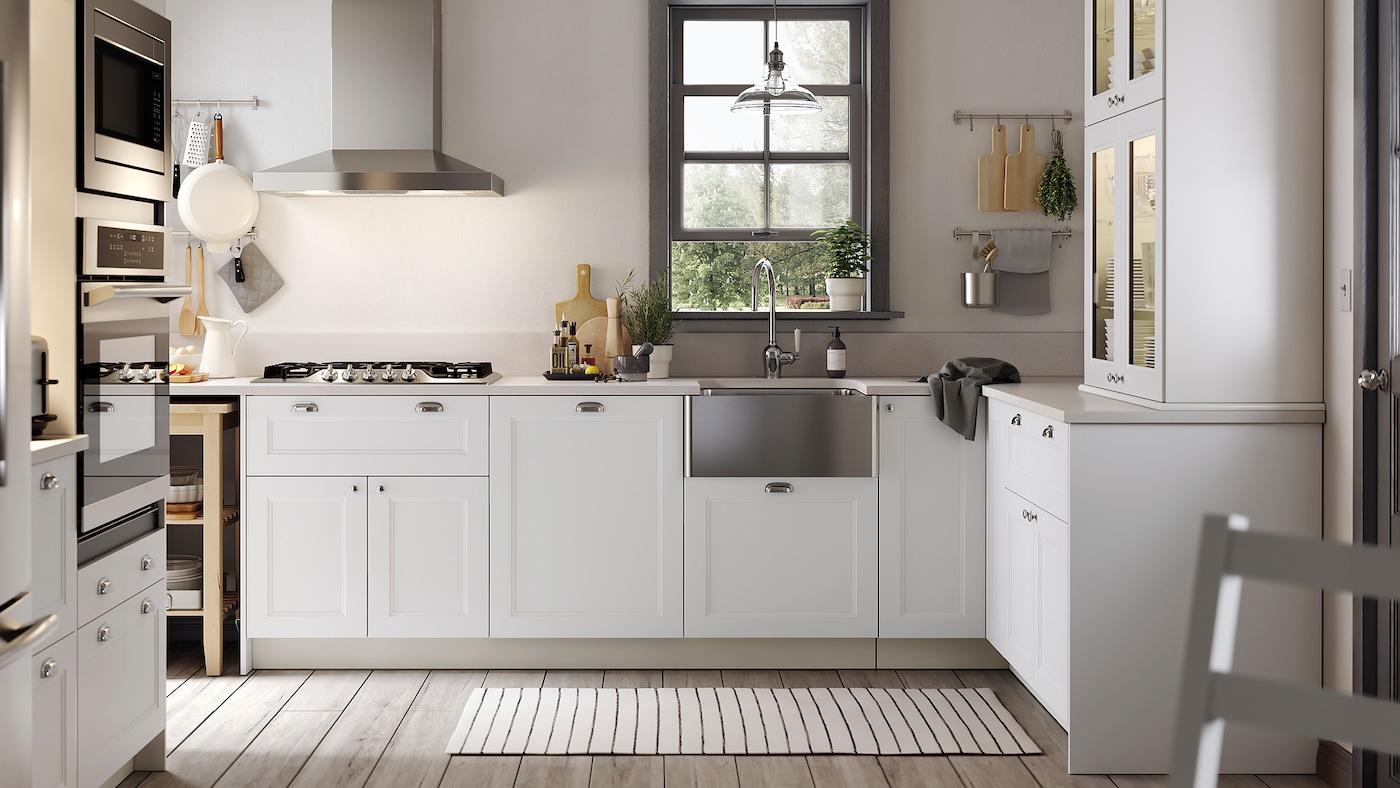 Une cuisine blanche avec des tiroirs blancs, des armoires à portes vitrées, un évier à tablier en inox.