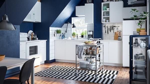 Une cuisine blanche dans un loft aux murs bleus avec des armoires blanches. Une desserte repose sur un tapis rayé au centre de la pièce.