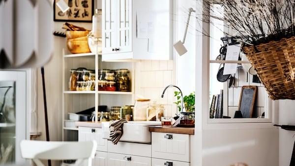 Une cuisine blanche de style campagnard avec des armoires METOD dotées de façades STENSUND, un évier blanc et des étagères accueillant bocaux et ustensiles.