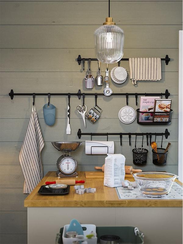 Une cuisine dans laquelle se trouve un îlot pourvu d'un comptoir en bois et un mur muni de longs supports noirs