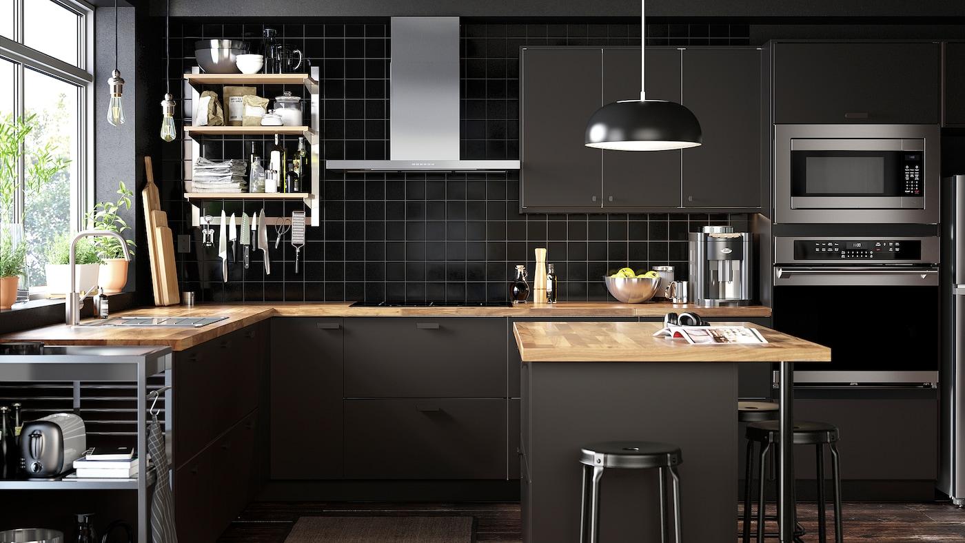 Une cuisine élégante comportant un support suspendu ouvert avec tablettes, des tiroirs KUNGSBACKA fermés en anthracite et une desserte sur roulettes.
