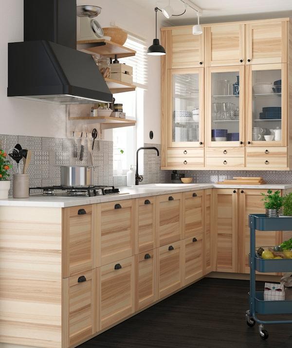 Une cuisine en bois avec un plan de travail blanc et une hotte noire.