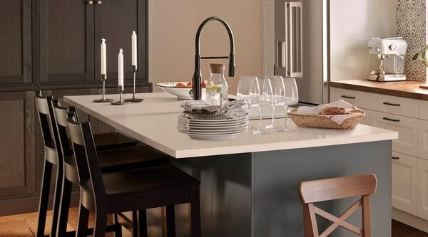 Une cuisine en gris foncé avec un îlot de cuisine avec comptoir en quartz et tabourets de bar noirs.